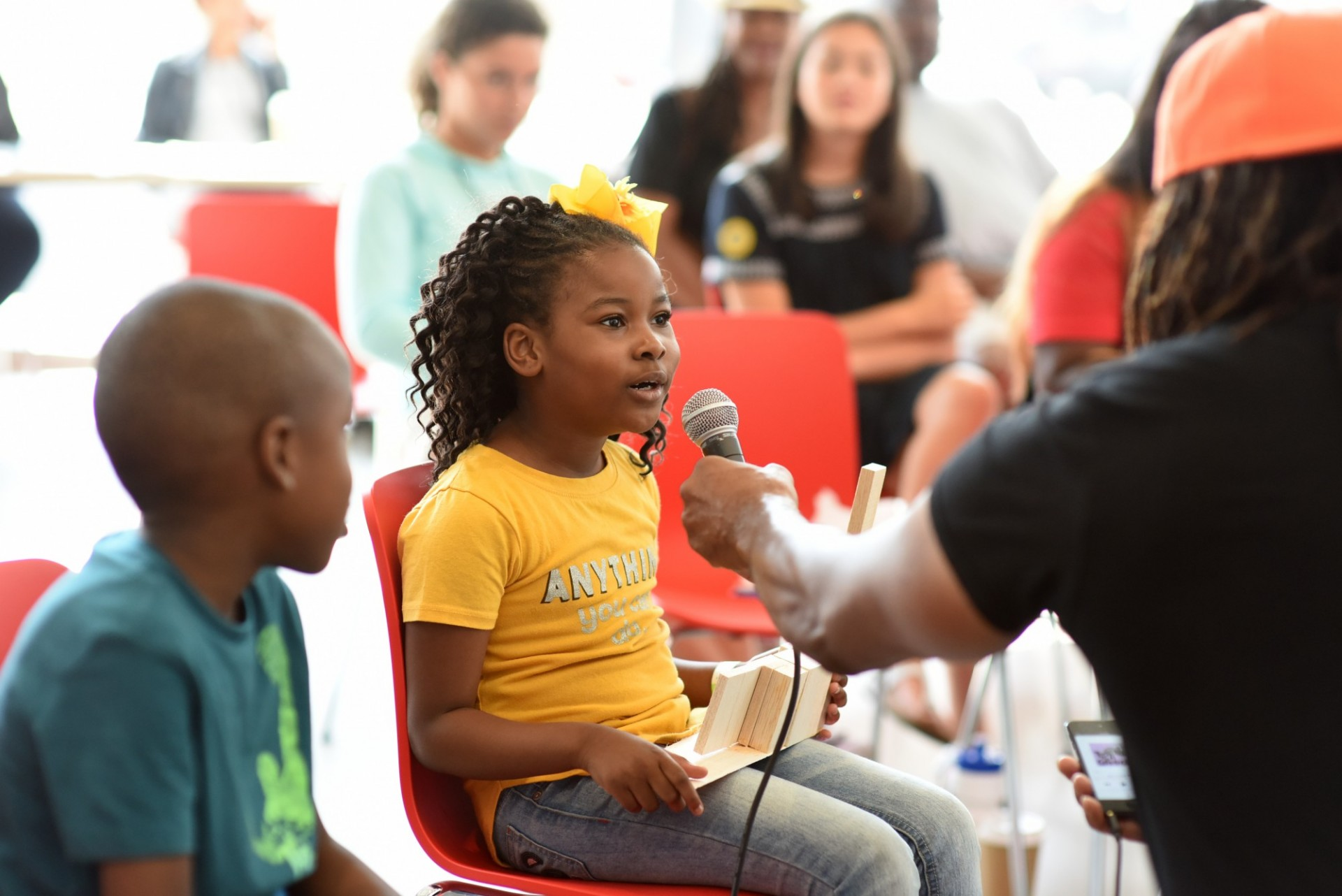 Instructor holds a microphone up to a young child in the audience during Community Day at The Forum