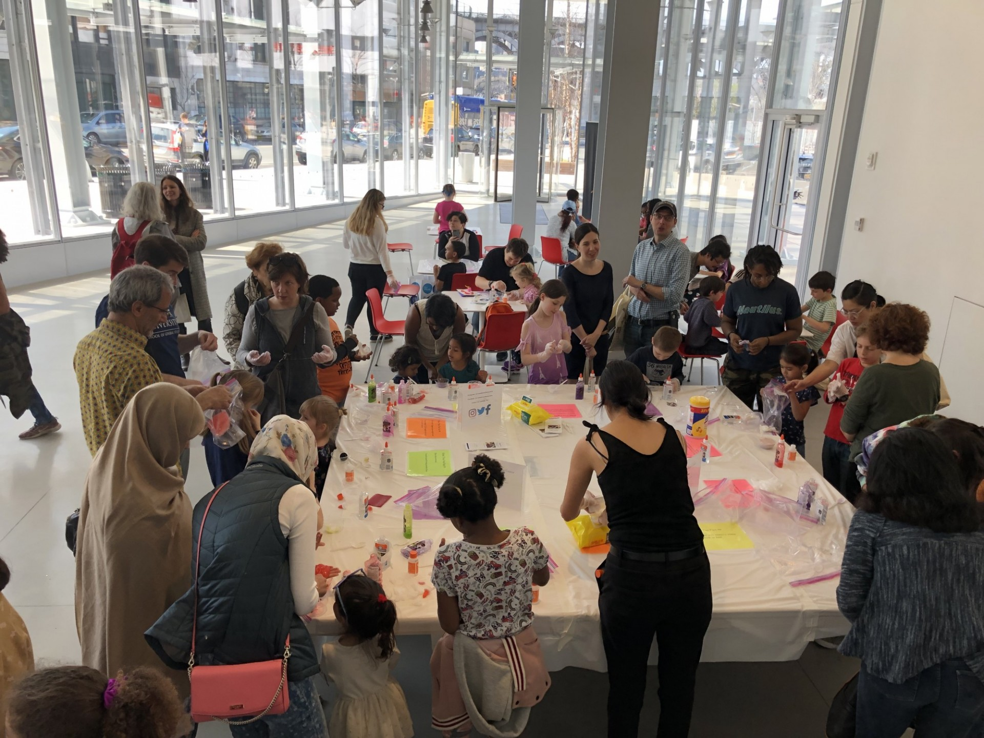 Group of children and adults gathered around a large square table making slime as part of Community Day at The Forum