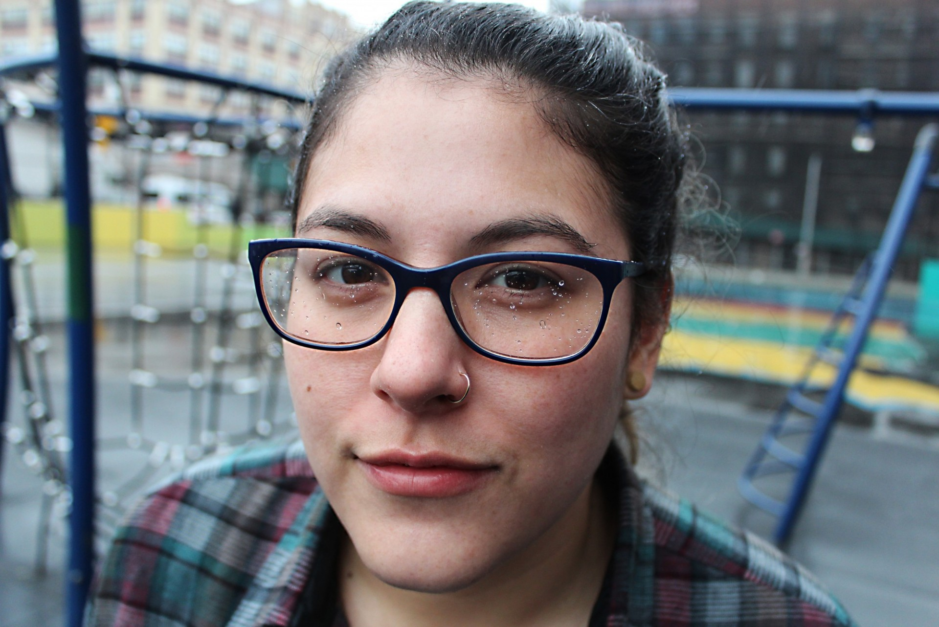 Close-up portrait of a young woman wearing glasses, with a playground in the background