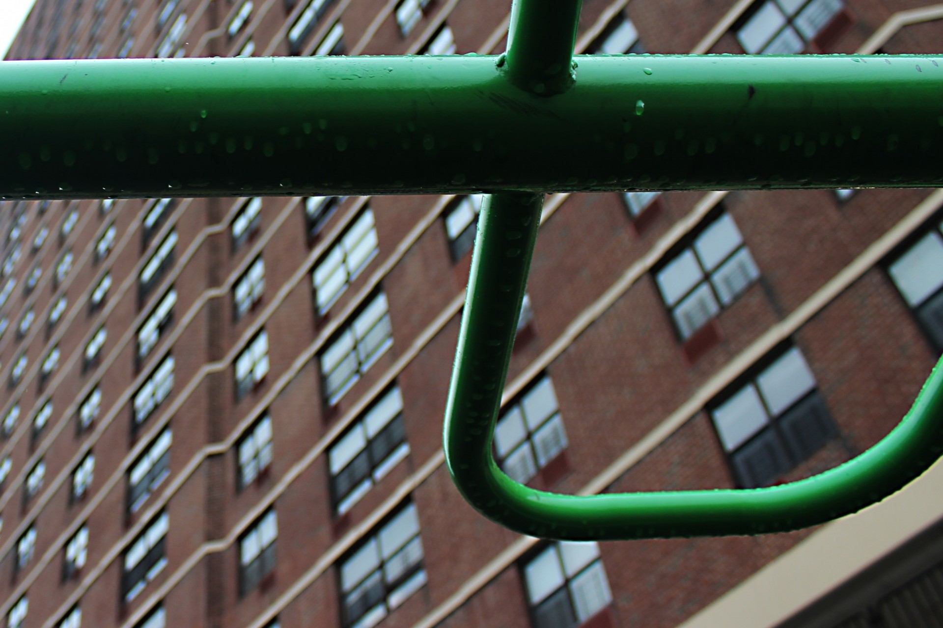 Close-up of raindrops on a green metal cross-bar, perhaps on a playground. A large apartment building with many windows looms in the background.