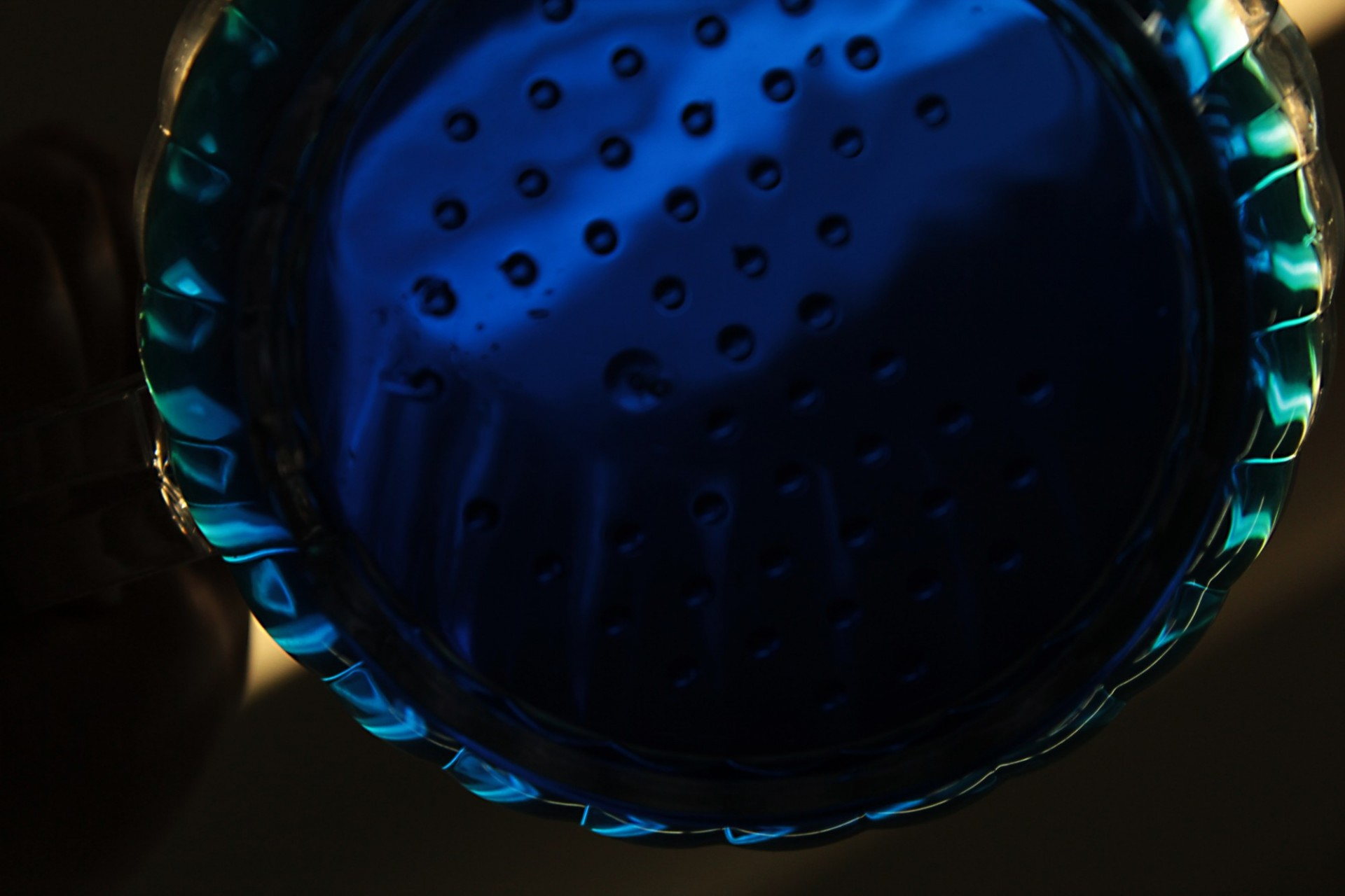 Close-up, dark image of a hard-to-distinguish round object, perhaps a shower head